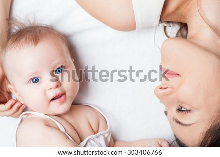Happy baby girl lying near her mother on a white bed. Newborn looking at the camera and smiling. Mothercare is most important in baby life