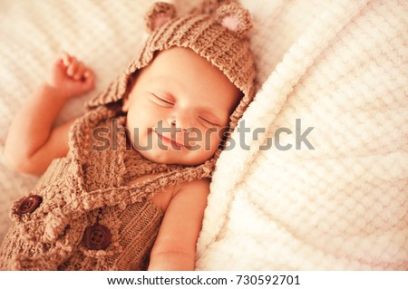 Happy baby girl 2-3 months old wearing knitted hat and suit sleeping in bed close up. Good morning. Happiness. Childhood.
