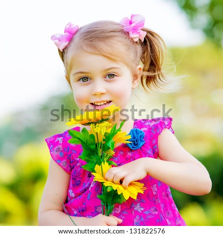 Happy baby girl playing outdoor, cute child holding fresh sunflower flowers, kid having fun in summer park, lovely smiling toddler portrait, enjoying nature of garden