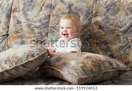 Happy baby girl sitting on a sofa among pillows