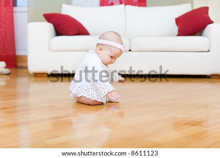 Happy baby girl touching a hardwood floor