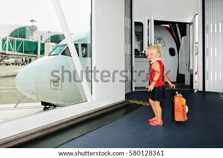 Happy baby girl wait for boarding to flight in departure gate from airport transit hall and looking through window at airplane. Active lifestyle, travel by air with child on family summer vacation.