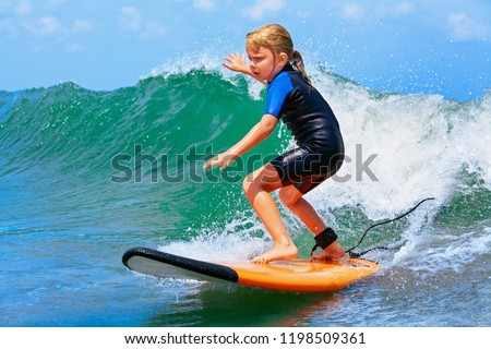 Happy baby girl - young surfer ride on surfboard with fun on sea waves. Active family lifestyle, kids outdoor water sport lessons and swimming activity in surf camp. Summer vacation with child. #1198509361