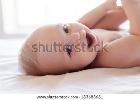 Happy baby. Happy little baby smiling at camera while lying in bed