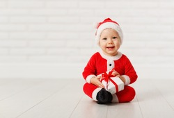 Happy baby in a Christmas costume Santa Claus with gifts on white brick  wall