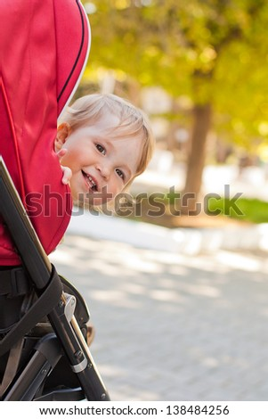 happy baby in a stroller looks out laughing in the park