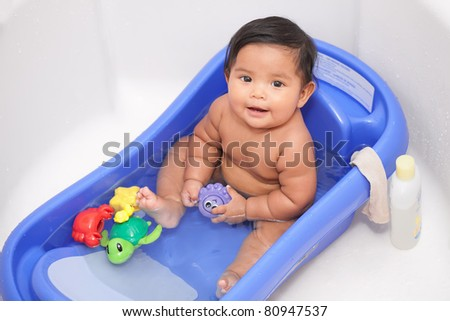 Happy baby in bathtub with water toys