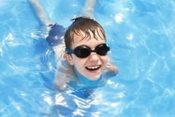 happy baby in the pool. boy swims in the pool with swimming glasses. . boy learning to swim