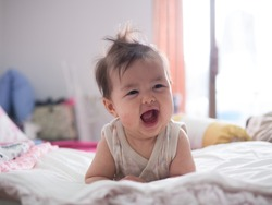 Happy baby is laughing while lying on the bed. Happy baby concept.
