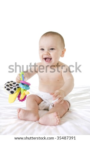 Happy baby laughing and smiling with colourful toy on white