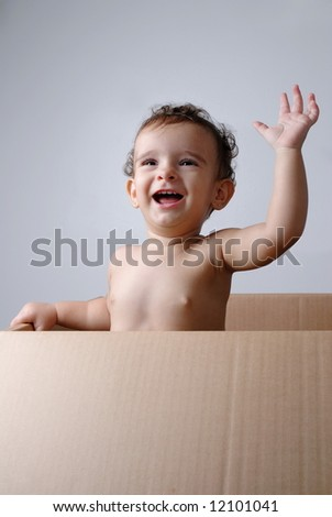Happy Baby leaving a cardboard box .