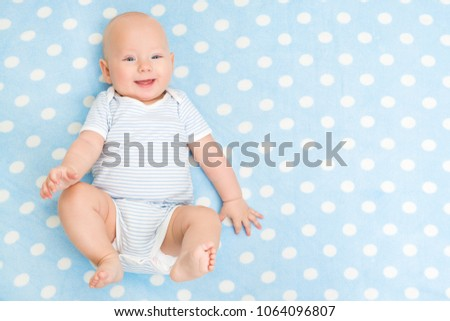 Happy Baby lying on Blue Carpet Background, Top View, Smiling Infant Kid Boy dressed in Bodysuit on spotted blanket, six months old child