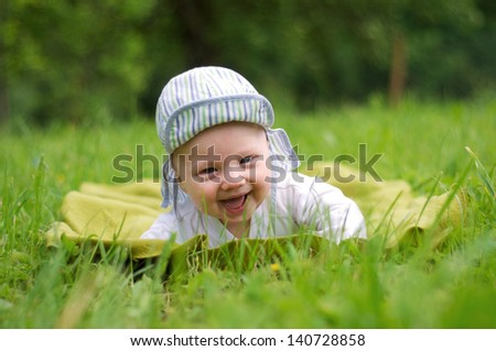 Happy baby lying on the grass