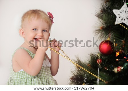 Happy baby near the Christmas tree with ornaments. Christmas. Child smiles and holds beads. A little girl.