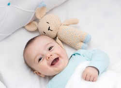 Happy baby newly awake in his crib and with his bunny doll. Light blue pajama and white bed sheets.