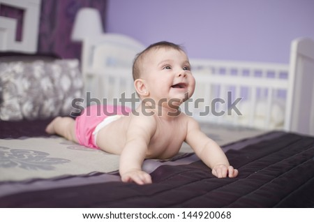 Happy Baby On A Bed, Lying And Smiling.