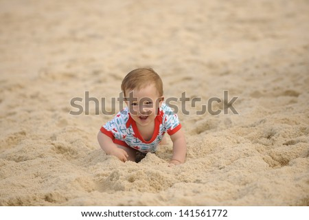 Happy baby on the beach crawling in the sand