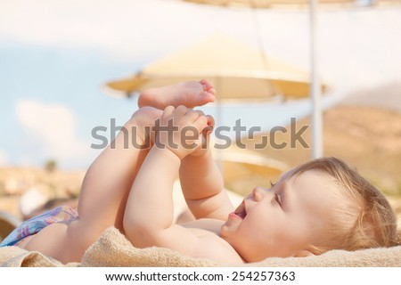 Happy baby on the beach sunbed. 8 month old kid lying on a sun lounger and playing with her feet. Summer holidays concept.