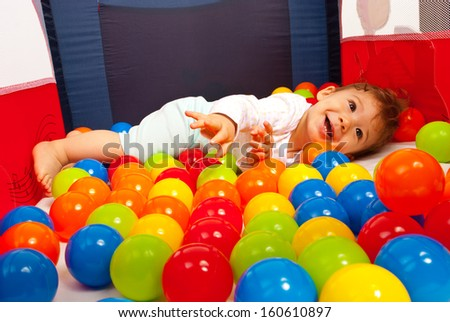 Happy baby playing with balls inside playpen