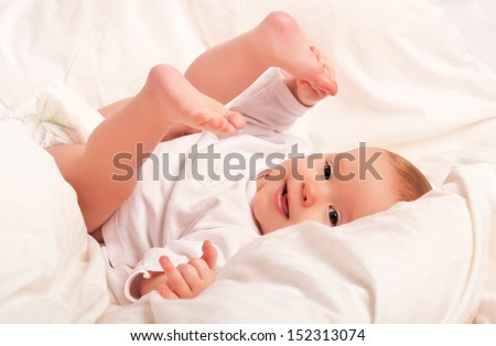 Happy baby plays with his legs in bed