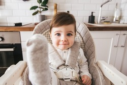 Happy baby sitting in high chair in a white kitchen. Healthy nutrition for kids. Children , the safety of children. Little boy play and ready to have lunch at home side view