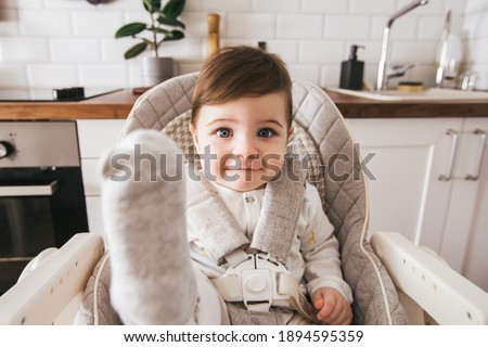 Happy baby sitting in high chair in a white kitchen. Healthy nutrition for kids. Children , the safety of children. Little boy play and ready to have lunch at home side view Stock foto ©