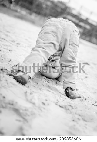 happy baby toddler standing upside down on the beach  ( black and white )
