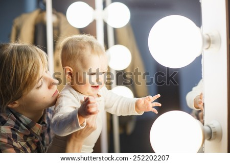happy baby wants to touch light bulb at makeup mirror