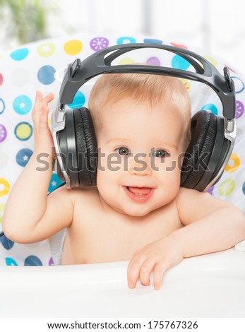 happy baby with headphones listening to music - stock photo