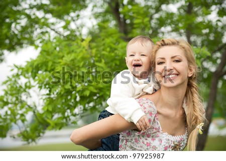 happy baby with mother on a background of green leaves. Much of copyspace