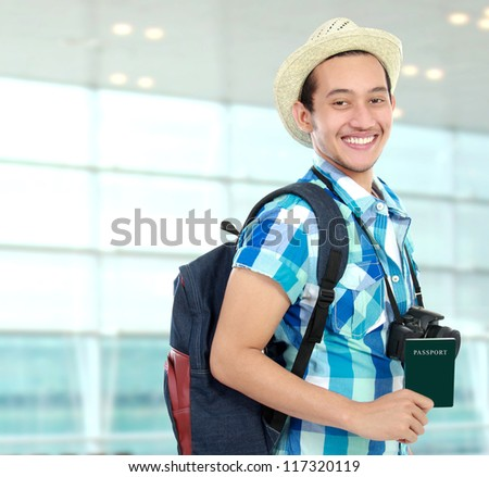 Happy backpacker at the airport terminal holding passport
