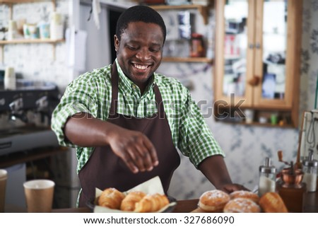 Happy baker powdering buns with vanilla sugar