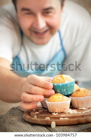 Happy baking. Chef is decorating delicious organic muffins. Almond and cherry cup cakes in natural setting.