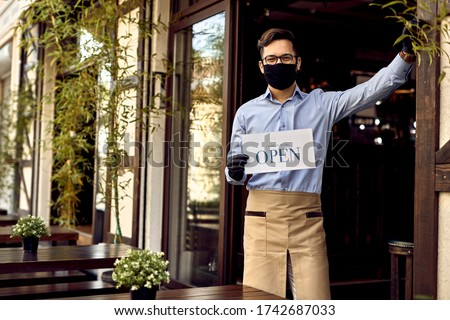 Happy barista holding open sign while wearing protective face mask and gloves at cafe's doorway.