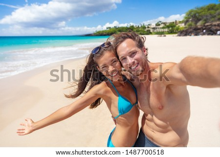 Happy beach couple selfie having fun smiling on Hawaii vacation suntan fit body Asian bikini girl excited with open arms smiling, man taking photo with phone.
