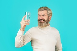 Happy beard man drinking water. Male drinking from a glass of water. Health care concept, lifestyle, close up. Smiling male holding transparent glass in her hand.