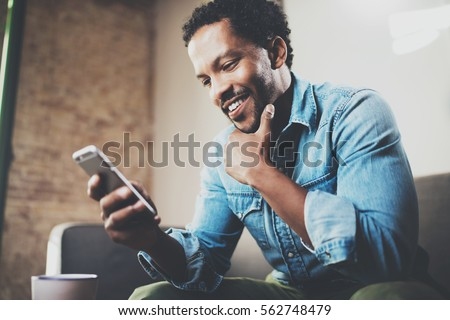 Happy bearded African businessman using phone while sitting on sofa at his modern home.Concept of young people working mobile devices.Blurred background - Shutterstock ID 562748479