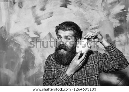 Happy bearded man, caucasian hipster, with long beard and moustache in red plaid shirt putting banknote in pink ceramic piggy bank on abstract colorful wall background. Saving money concept #1264693183