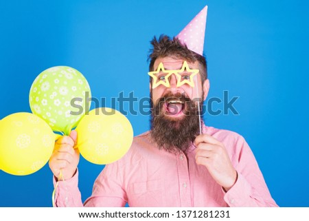 Happy bearded man in birthday cap with colourful baloons and paper star shaped glassses. Comedian with long beard and open mouth performing show. Bearded man entertaining guests at party, fun concept.