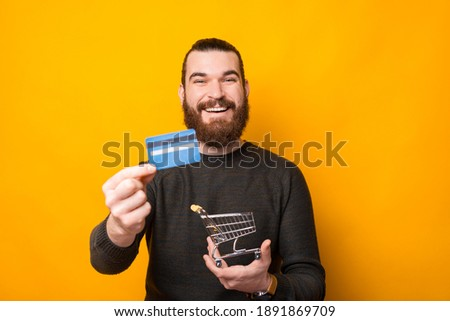 Happy bearded man in casual standing over yellow background showing credit card and holding shopping trolley