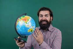 happy bearded man in checkered shirt looking at geographic globe, geography school education