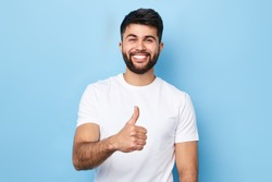 Happy bearded man in stylish white T-shirt with beaming smile showing thumb up, isolated over blue background, studio shot. good job, well done. agreement concept