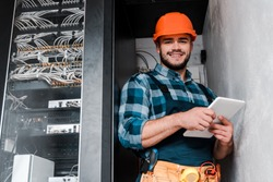 happy bearded technician in safety helmet holding digital tablet