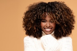 Happy beautiful african girl with afro hairstyle posing in cozy sweater on beige studio background.