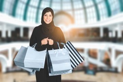 Happy beautiful Arabic woman wearing abaya and hijab with shopping bags stands at mall. Attractive Arabian girl with purchasing bags in big mall