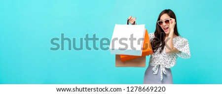 Happy beautiful Asian shopaholic woman carrying shopping bags in colorful light blue banner background with copy space for summer sale concept