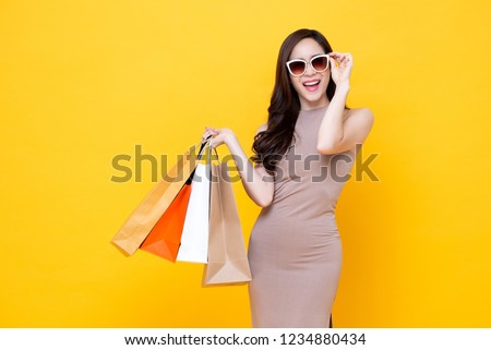 Happy beautiful Asian shopaholic woman carrying shopping bags in colorful yellow background, summer sale concept