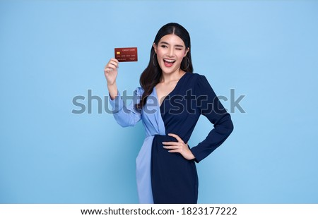 Happy beautiful Asian shopaholic women wearing blue dress showing credit card in hand isolated on blue background.