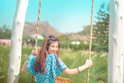 Happy beautiful Asian woman having relax time on a swing in nature field for nature hapiness lifestyle