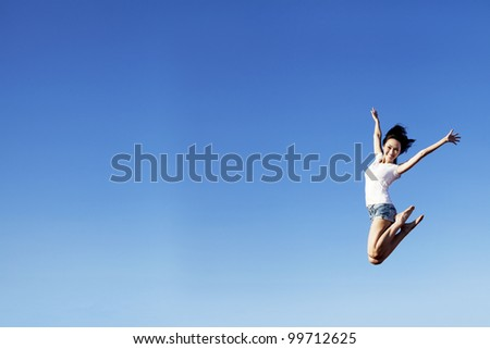 Happy beautiful asian woman jumping with copy space. Shot over clear blue sky can be used to add your text